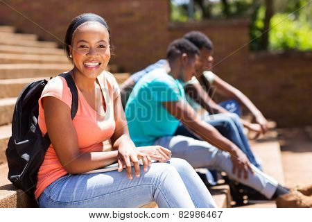 pretty female afro american college student sitting on steps