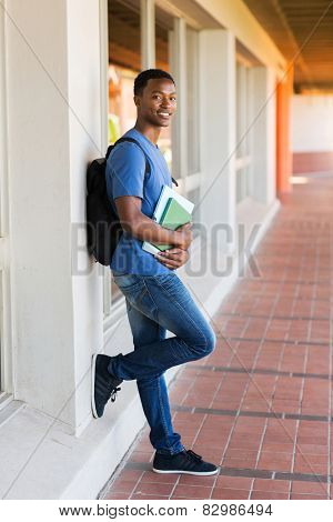handsome african college student leaning against wall
