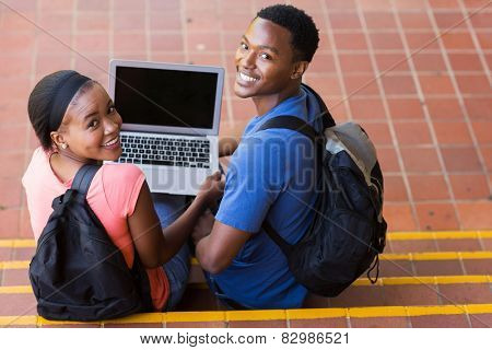 happy young african college couple with laptop computer