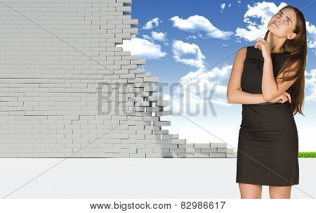 Thoughtful businesswoman in dress looking up. Dilapidated brick wall, green meadow with sky as backd