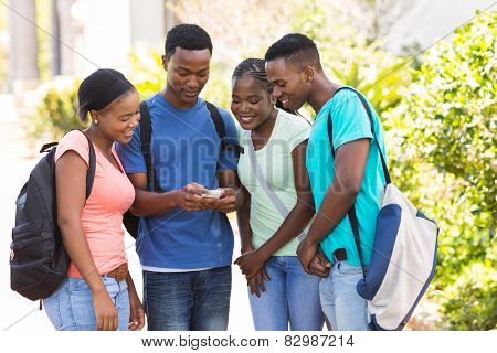 group of cute african american college students using cell phone on campus