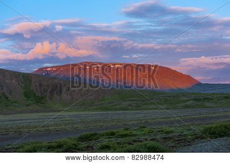 A single mountain lit by a setting sun. The color of the mountain is red while rest of the landscape is being covered by evening shadows. Iceland