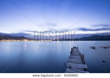 A Romantic Blue Sunset With A Jetty Over A Lake With An Evening Glow