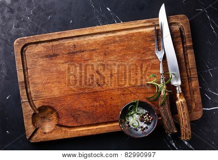 Chopping Cutting Board, Seasonings And Rosemary With Fork And Knife Carving Set On Dark Marble Backg