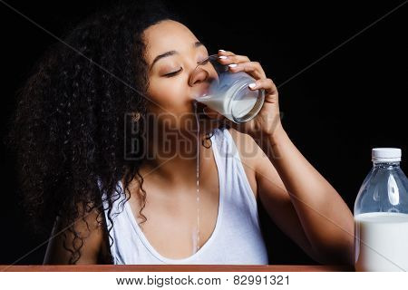 African cheerful girl with a glass of milk on dark background,