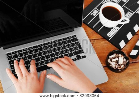 Female hands of scriptwriter working on laptop at wooden desk background