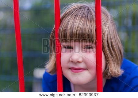 Head of young girl behind red bars