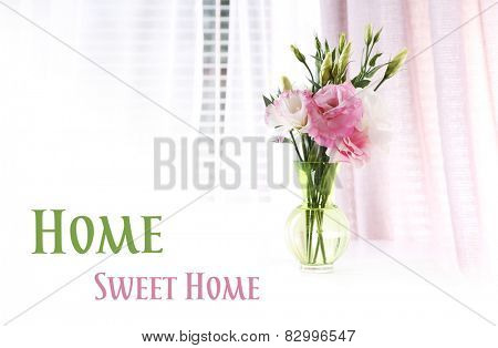 Beautiful flowers in vase with light from window and space for your text