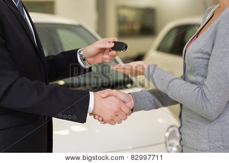 Businessman giving car key while shaking a customer hand at new car showroom