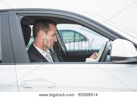 Serious businessman reading a map in his car