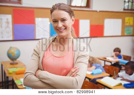 Pretty teacher smiling at camera with arms crossed at the elementary school