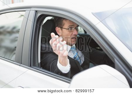 Handsome businessman experiencing road rage in his car