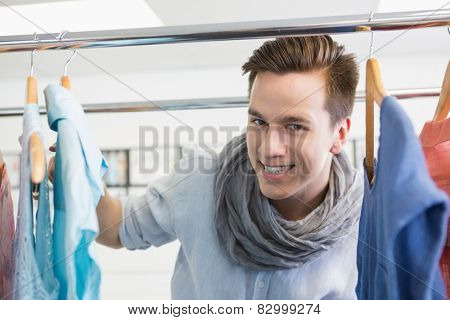 Smiling student near clothes rack at the college
