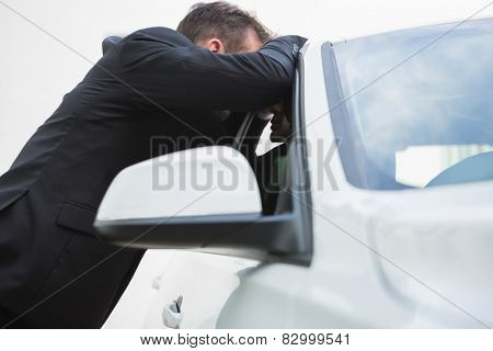 Businessman looking inside the car in a car park
