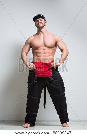 muscular construction worker in overalls