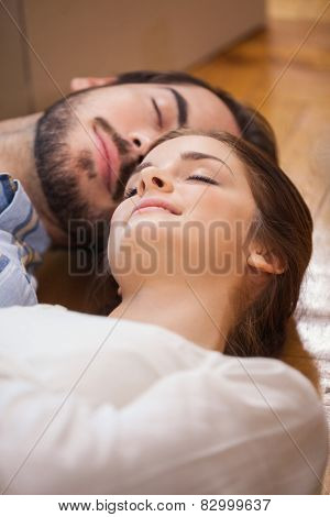 Cute couple sleeping on the floor in their new home