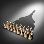 stock photo of leader  - Company leadership and team management vision as a business group concept with chess set pieces joining and working together united and as one in agreement to cast a shadow shaped as 