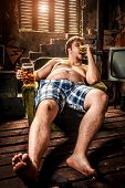 picture of beer-belly  - fat man eating hamburger seated on armchair - JPG