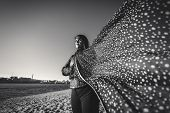 stock photo of windy  - Black and white wide angle portrait of elegant woman in scarf at windy day on beach - JPG