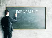 stock photo of impossible  - businessman drawing impossible on a chalk board