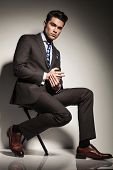 stock photo of side view  - Side view picture of a young elegant business man sitting with one leg in front of the other - JPG