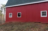 image of red barn  - Brown horse looks out the window of a red barn to say Hello - JPG