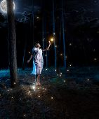 stock photo of fireflies  - Lost young woman at night forest with full moon jumping high to reach firefly - JPG
