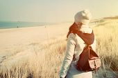 picture of knapsack  - Woman with retro backpack standing on the beach - JPG