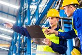 stock photo of forklift driver  - Worker and forklift driver in industrial factory looking at camera - JPG