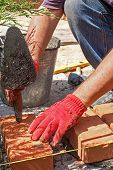 foto of bricklayer  - Bricklayer with brick at a construction site - JPG