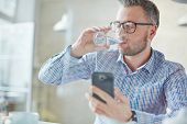 pic of sms  - Businessman in casualwear drinking water while reading sms or dialing number on cellphone - JPG