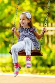 stock photo of seesaw  - Pretty little girl swinging on seesaw in summertime - JPG