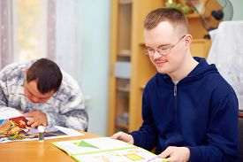 foto of daycare  - young adult man engages in self study in rehabilitation center - JPG