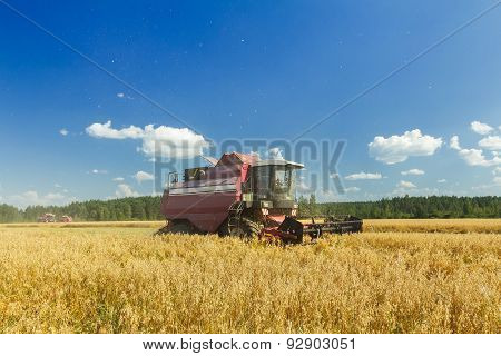 Modern Combine Harvester Working On Oats Farm Field Under Blue Sky In Hot Summer Day