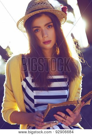 Fashion hipster girl read book on nature background