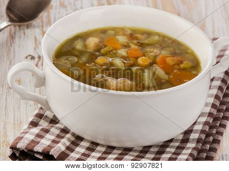 White Bowl Of Soup With Lentils, Beans, Chicken And Vegetables.