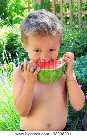 Four year old shirtless boy eating a watermelon outside.