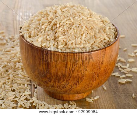 Raw Uncooked Brown Rice In Wooden Bowl.