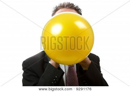 Facing Businessman Blowing Up  A Balloon