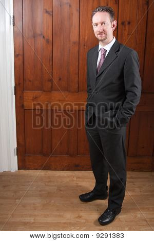 Full Length Businessman With Wood Panels