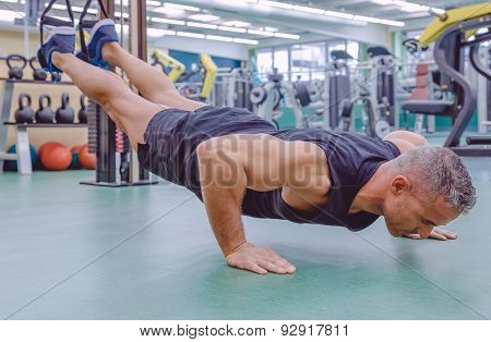 Man doing suspension training with fitness straps