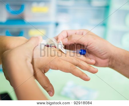 Closeup Of Hands Attaching Intravenous Tube To Patient's Hand In Hospital.