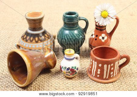 Decorative Ceramic Vases And White Daisy On Jute Canvas