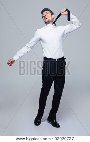 Full length portrait of a happy young businessman to hang himself with tie over gray background