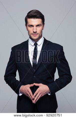Confident young businessman standing over gray background and looking at camera