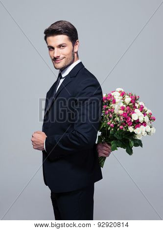 Businessman hiding bouquet of flowers behind his back over gray background and looking at camera