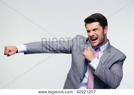 Angry businessman fighting and shouting over gray background