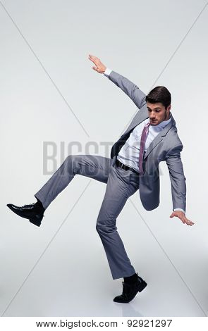 Handsome businessman flying over gray background and looking down
