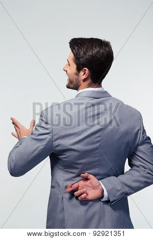 Back view portrait of a businessman with fingers crossed over gray background