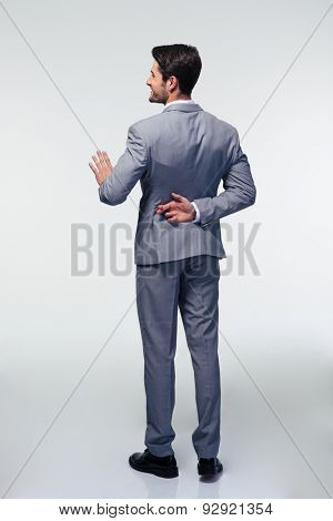 Full length portrait of a businessman with fingers crossed behind back over gray background